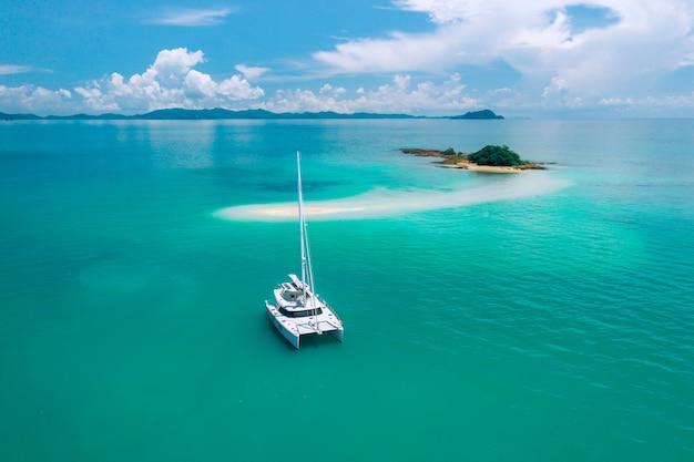 Eine einsame segelyacht, die im azurblauen warmen ozean treibt und auf eine mysteriöse grüne insel mitten im ozean zusteuert. reisen. luxusurlaub. warmer ozean. paradies. tourismus.