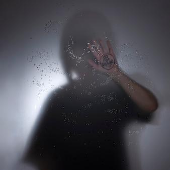 Eine einsame silhouette einer depressiven jungen frau mit einer ausgestreckten hand, die sagt