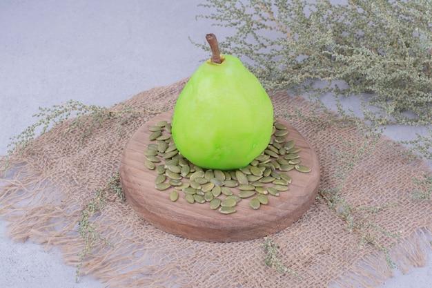 Eine einzelne grüne birne auf einem holzbrett mit kürbiskernen herum