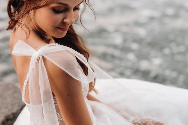 Eine elegante braut in einem weißen kleid, handschuhen und nackten füßen sitzt in der nähe eines wasserfalls im park und genießt die natur. ein modell in hochzeitskleid und handschuhen in einem naturpark. weißrussland