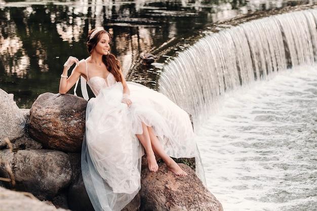 Eine elegante braut in einem weißen kleid, handschuhen und nackten füßen sitzt in der nähe eines wasserfalls im park und genießt die natur.