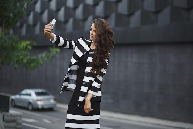 Eine elegante junge frau in einem schwarzweiss-kleid, das ein selfie mit einem handy nimmt