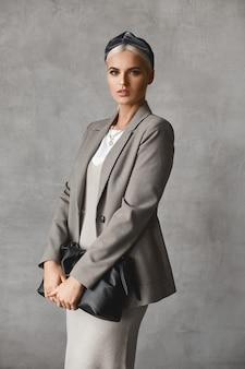 Eine elegante vorbildliche frau mit perfektem make-up, die ein gestricktes kleid und einen blazer trägt, geldbörse hält und über grauer wand posiert