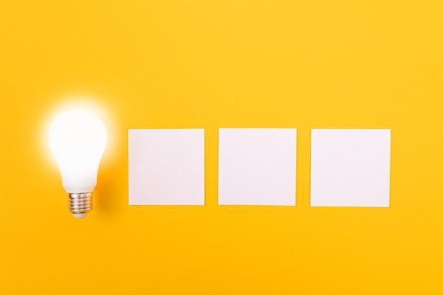 Eine energiesparlampe mit weißem notizpapier