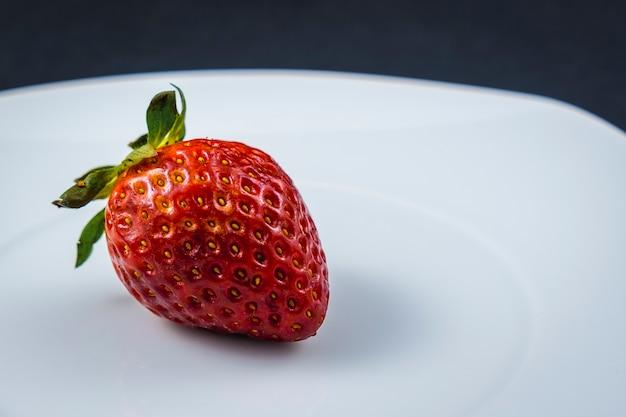 Eine erdbeere auf einem weißen teller. gutes und gesundes essen