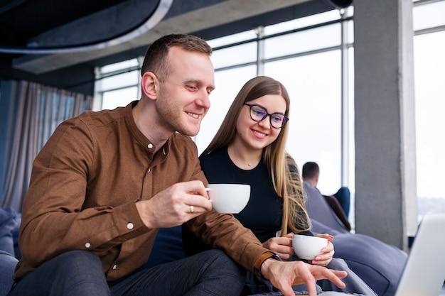 Eine erfolgreiche junge managerin mit ihrem chef sitzt mit einem laptop auf einem polstersessel am panoramafenster und trinkt kaffee. geschäftsfrau und -mann, die an einem neuen projekt arbeiten