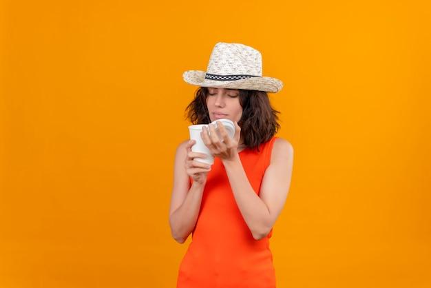 Eine erfreute junge frau mit kurzen haaren in einem orangefarbenen hemd, das einen sonnenhut trägt, der plastikbecher öffnet und kaffee riecht