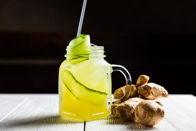 Eine erfrischende sommerlimonade mit gurke und ingwer in einem glas auf weißem holztisch