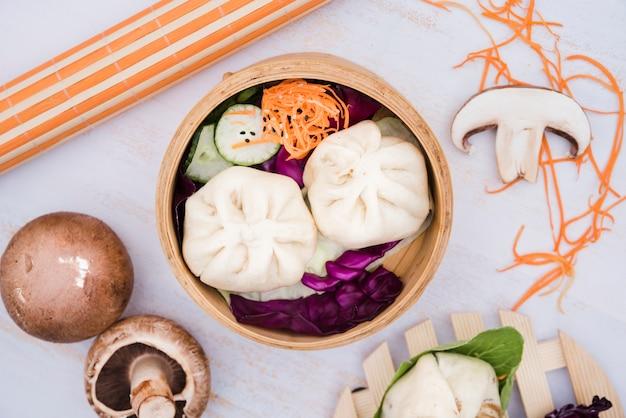Eine erhöhte ansicht der dampfmehlklöße und des salats im bambusdampfer