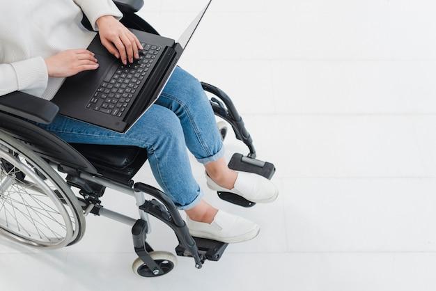 Eine erhöhte ansicht der frau, die laptop auf dem rollstuhl verwendet