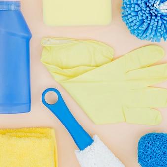 Eine erhöhte ansicht der gelben handschuhe; schwamm; flasche; serviette auf pfirsich hintergrund