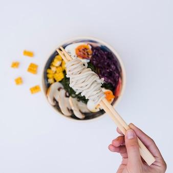 Eine erhöhte ansicht der hand einer person, die nudeln auf essstäbchen über der asiatischen küche hält