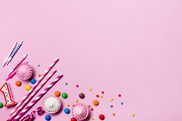 Eine erhöhte ansicht der trinkhalme; kerzen; edelsteine; luftschlangen und streusel an der ecke des rosa hintergrunds