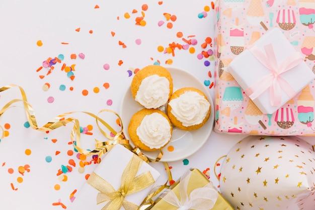 Eine erhöhte ansicht des dekorativen cupcakes mit geschenken; partyhut; streamer und konfetti auf weißem hintergrund