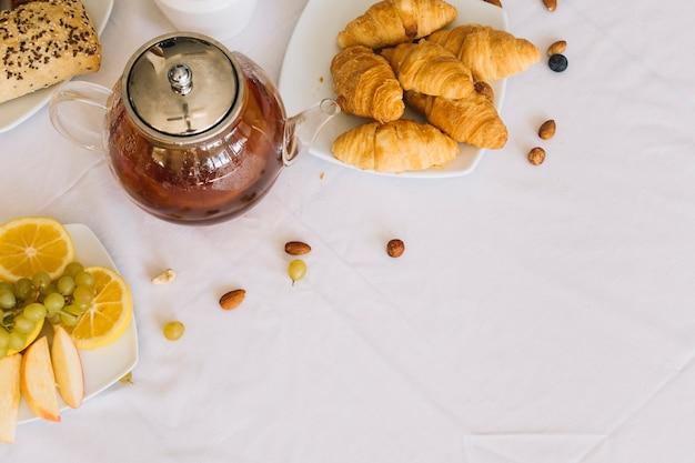 Eine erhöhte ansicht des gebackenen hörnchens; früchte; tee und dryfruits auf weißer tischdecke