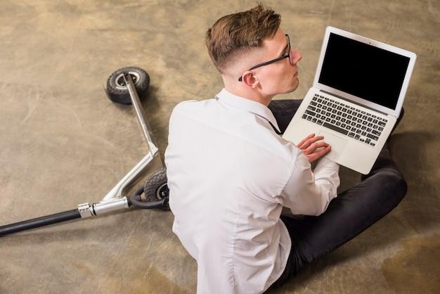 Eine erhöhte ansicht des jungen mannes laptop in der hand halten, der auf fußboden sitzt