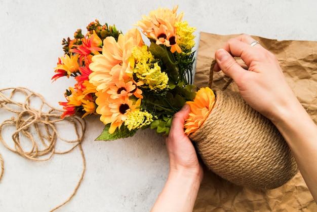 Eine erhöhte ansicht einer frau, die die vase mit schnur macht