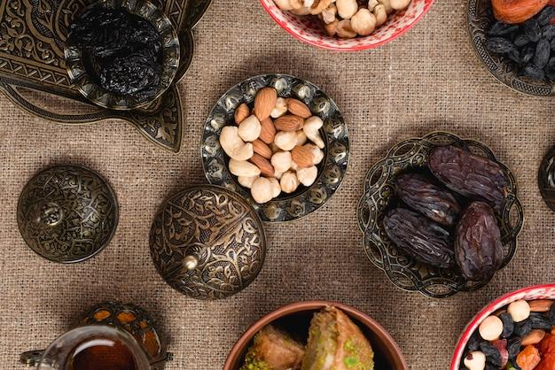 Eine erhöhte ansicht von datumsangaben; nüsse und rosinen auf einer metallischen schüssel über der tischdecke