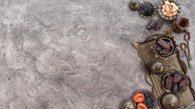 Eine erhöhte ansicht von datumsangaben; nüsse und rosinen auf metallischem behälter über dem grauen konkreten hintergrund