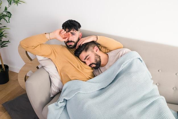 Eine erhöhte ansicht von den homosexuellen paaren, die sich zu hause auf sofa entspannen