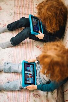 Eine erhöhte ansicht von den kleinkindern, die video auf digitaler tablette aufpassen