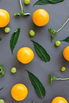 Eine erhöhte ansicht von ganzen orangen; trauben; blatt und zweige auf grauem hintergrund
