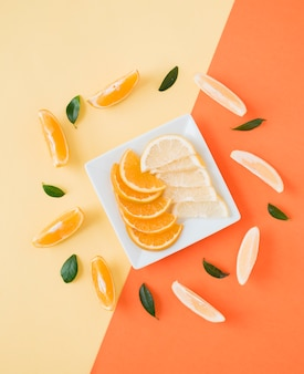 Eine erhöhte ansicht von orangen- und zitronenscheiben auf platte über dem doppelhintergrund