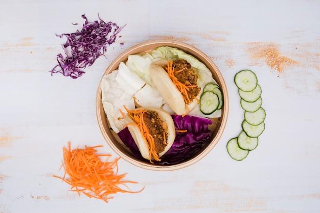 Eine erhöhte ansicht von taiwans traditionellem lebensmittelgua bao im dampfer mit salat auf hölzernem beschaffenheitshintergrund