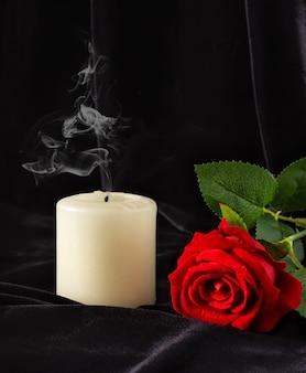 Eine erloschene kerze und eine rote rose auf einer schwarzen oberfläche