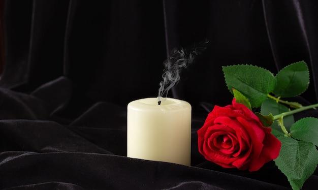 Eine erloschene kerze und eine rote rose auf schwarzem hintergrund