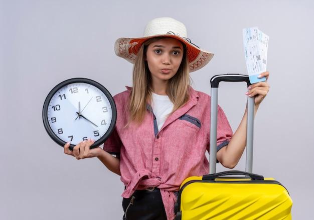 Eine ernste junge frau, die rotes hemd trägt, das wanduhr gelben koffer und flugtickets beim betrachten auf einer weißen wand hält