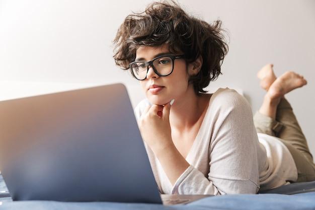 Eine ernsthafte junge frau liegt drinnen mit einem laptop auf dem bett.
