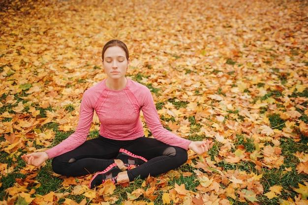Eine ernsthafte und konzentrierte junge frau sitzt im lotussitz und hält die augen geschlossen. sie ist ruhig und friedlich. frau sitzt auf boden voller blätter. es ist herbst draußen.