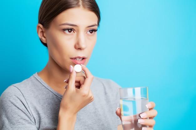 Eine erschöpfte frau, die unter zahnschmerzen leidet, nimmt ein schmerzmittel