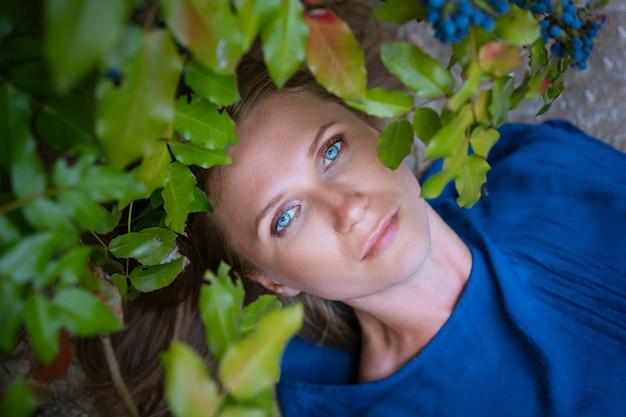 Eine erwachsene blonde frau mit blauen augen liegt in den blättern.