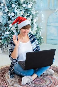 Eine erwachsene frau, die einen weihnachtsmannhut trägt, sitzt nahe einem weihnachtsbaum mit einem laptop