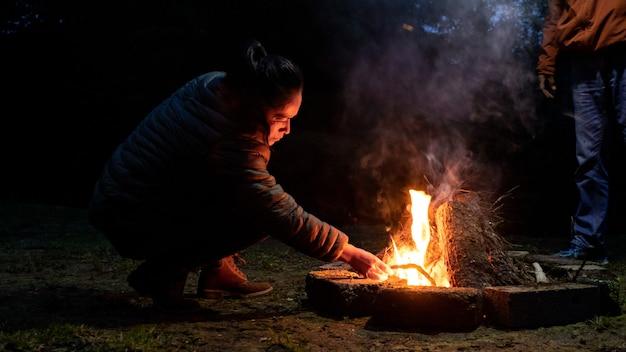 Eine erwachsene frau zündet nachts mitten im wald ein lagerfeuer an