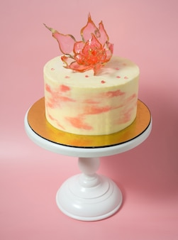 Eine essbare rote blume auf einem isomaltkuchen auf rosa hintergrund