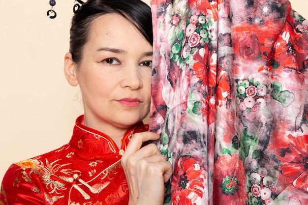Eine exquisite japanische geisha der front geschlossene ansicht in traditionellem rotem japanischem kleid, das mit elegantem lächeln des blumendesigns auf der cremefarbenen hintergrundzeremonie japan aufwirft