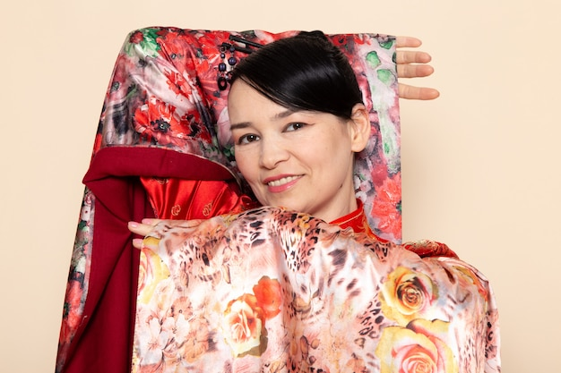 Eine exquisite japanische geisha der vorderansicht im traditionellen roten japanischen kleid, das mit dem eleganten lächeln des blumendesigngewebes auf der cremefarbenen hintergrundzeremonie japan aufwirft