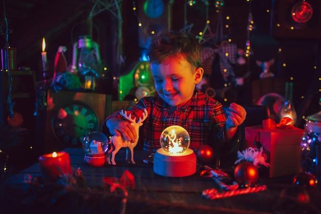 Eine fabelhafte, magische, weihnachtliche atmosphäre. ein kleiner junge, der assistent des weihnachtsmanns, sitzt an einem weihnachtlich geschmückten tisch. postkarte. farbiges licht