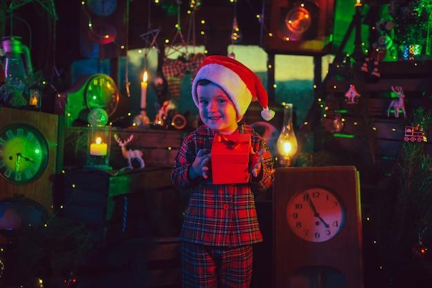 Eine fabelhafte, weihnachtliche atmosphäre. ein kinderjunge hält eine schachtel mit einem geschenk in den händen in den neujahrsdekorationen. farbiges licht. foto für eine postkarte.
