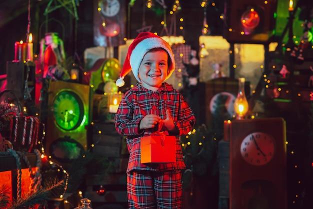 Eine fabelhafte, weihnachtliche atmosphäre. ein kinderjunge hält eine schachtel mit einem geschenk in den händen in den neujahrsdekorationen. foto für eine postkarte.