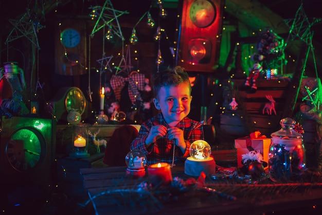 Eine fabelhafte, weihnachtliche atmosphäre. ein kleiner junge, der assistent des weihnachtsmanns, an den tischen mit geschenken. dekorationen für das neue jahr. postkarte. farbiges licht