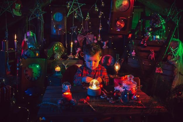 Eine fabelhafte, weihnachtliche atmosphäre. ein kleiner junge, der assistent des weihnachtsmanns, an den tischen mit geschenken. dekorationen für das neue jahr. postkarte.