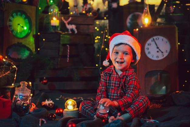Eine fabelhafte, weihnachtliche atmosphäre. fröhliches baby im schönen pyjama und weihnachtsmütze in weihnachtsdekorationen. foto für eine postkarte.