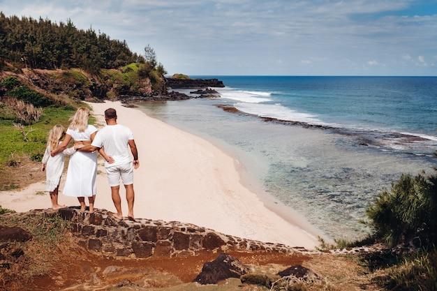 Eine familie in weiß mit drei personen blickt in die ferne des strandes gris gris auf der insel mauritius. die familie blickt auf die wunderschöne natur der insel mauritius und den indischen ozean.