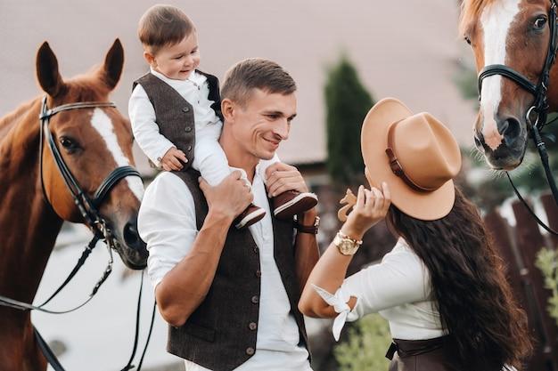 Eine familie in weißen kleidern mit ihrem sohn steht in der nähe von zwei schönen pferden in der natur
