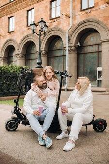 Eine familie in weißer kleidung steht in der stadt auf elektrorollern und trinkt einen drink