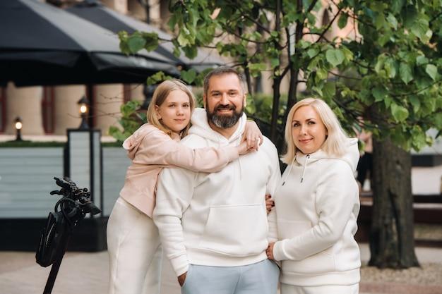 Eine familie in weißer kleidung steht in der stadt auf elektrorollern.